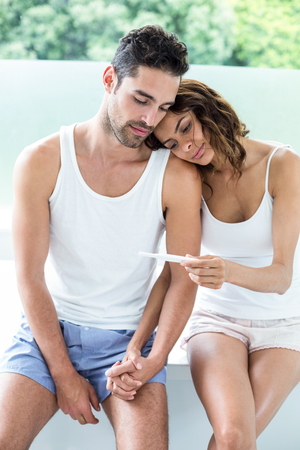 home pregnancy test: Wife showing pregnancy test to husband at home