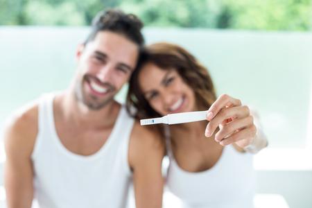 Portrait of happy couple showing pregnancy kit