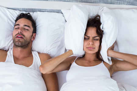 blocking: High angle view of woman blocking ears while man snoring on bed
