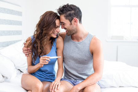 Happy young woman holding pregnancy test sitting besides husband in room Stock Photo
