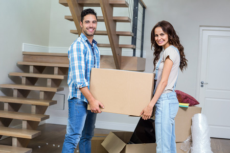 Portrait of smiling couple carrying cardboard box while standing at home