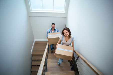 people moving: High angle portrait of smiling couple holding cardboard boxes while climbing steps of house Stock Photo