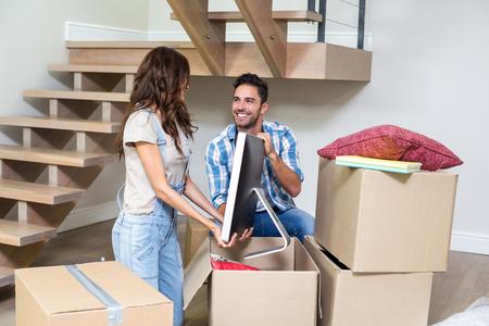 boite carton: Sourire couple déballage ordinateur à partir de la boîte en carton à la maison