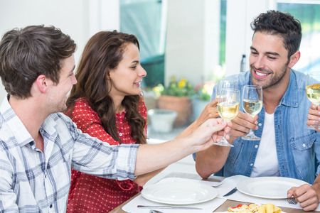 Happy friends toasting white wine at table