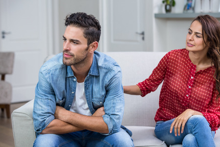 consoling: Woman consoling man after argument while sitting on sofa