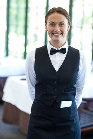 20s waitress: Happy waitress smiling at camera in a restaurant