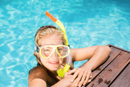 pool side: Portrait of happy woman with snorkel gear leaning on pool side on a sunny day