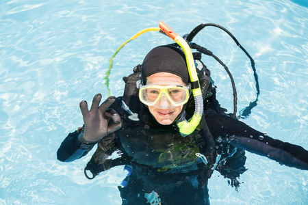 scuba woman: Young woman on scuba training in swimming pool showing ok gesture