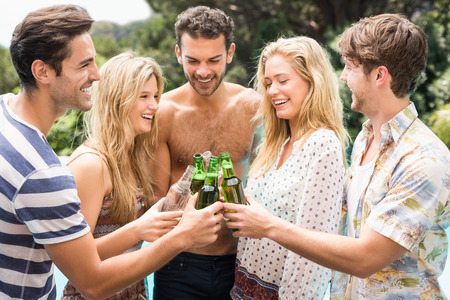 near beer: Group of friends toasting beer bottles while enjoying near pool