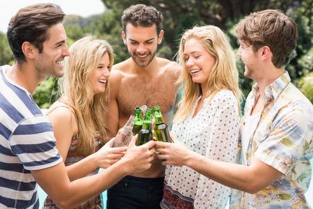 near beer: Group of friends toasting beer bottles while enjoying near pool