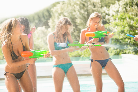water gun: Happy friends doing water gun battle near swimming pool