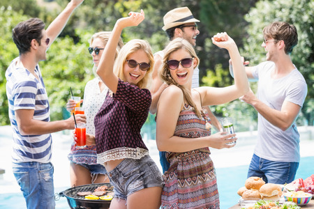 escapism: Group of friends dancing at outdoors barbecue party near pool