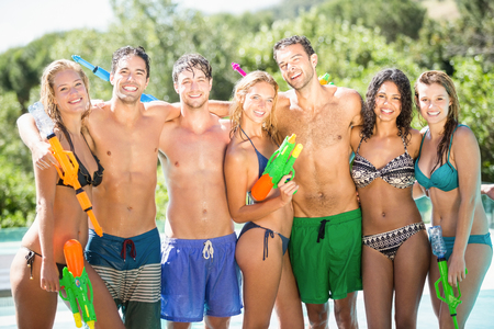 standing together: Happy friends standing together near swimming pool with water guns Stock Photo
