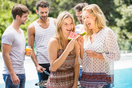 water melon: Young women smiling and having a slice of water melon while their friends preparing bbq behind