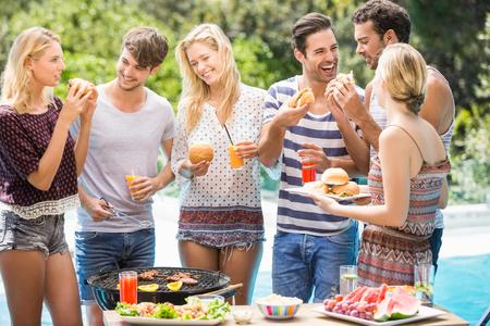 Skupina přátel, které mají hamburgery a šťávu na venkovní gril párty Reklamní fotografie