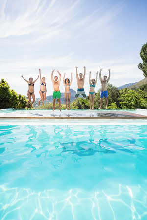 manos levantadas: Group of friends jumping at poolside with their hands raised Foto de archivo