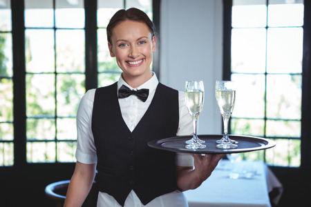 hotel service: Waitress with a tray of flute of champagne in a restaurant Stock Photo