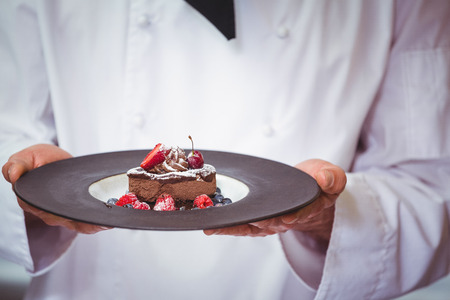 commercial kitchen: Chef holding a plate with a dessert in commercial kitchen