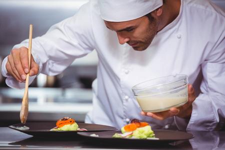 Chef-kok zetten saus op een schotel in een commerciële keuken Stockfoto