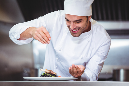 Chef sprinkling spices on dish in commercial kitchen Stock Photo