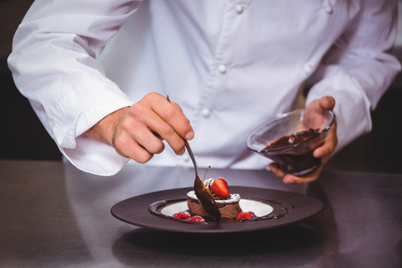uniform clothing: Chef putting chocolate sauce on a dessert in a commercial kitchen