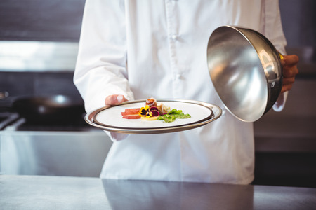 commercial kitchen: Chef raising a bell of a dish in commercial kitchen