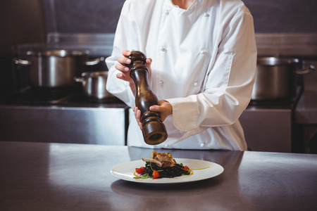 sprinkling: Chef sprinkling pepper on dish in a commercial kitchen Stock Photo