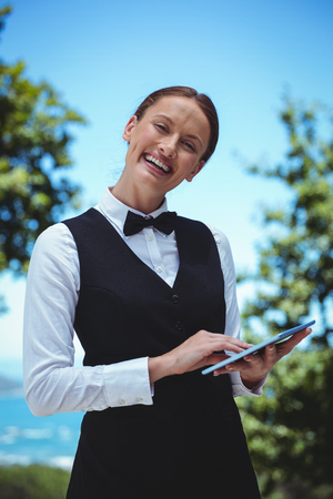Smiling waitress taking an order with a tablet in a restaurant Imagens - 54335352