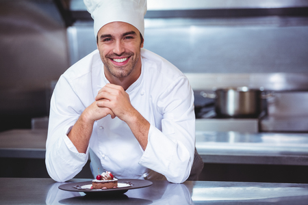 Chef leaning on the counter with a dessert in commercial kitchen Stock Photo