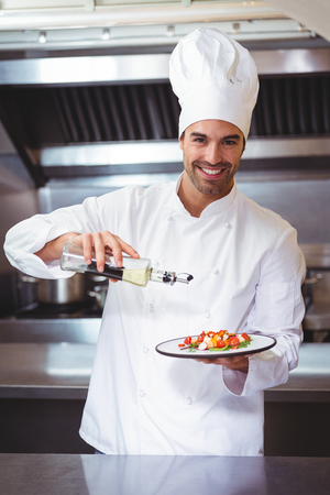 Chef putting finishing touch on salad in commercial kitchen Stock Photo