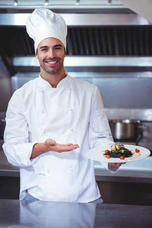 chef uniform: Chef showing his dish in commercial kitchen