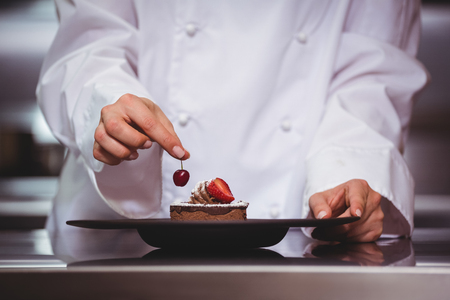 Chef putting a cherry on a dessert in a commercial kitchen Stock Photo