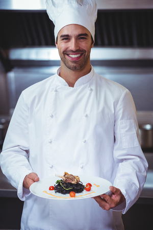 commercial kitchen: Chef holding his dish in commercial kitchen Stock Photo