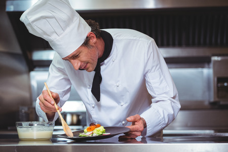 sauce dish: Chef putting sauce on a dish in a commercial kitchen
