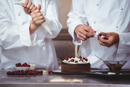 Chefs decorating a cake they just made in a restaurant