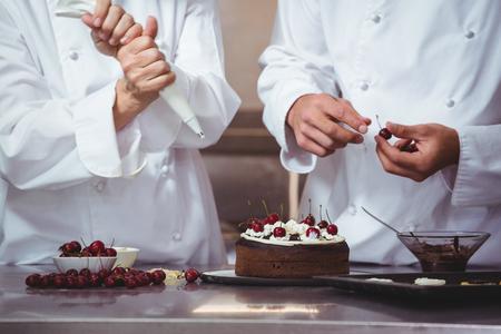 decoracion de pasteles: Chefs que decoran una torta que acaba de hacer en un restaurante