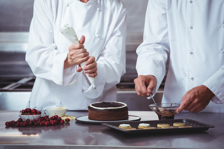 Chefs decorating a cake in a restaurant Stock Photo