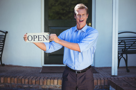 open sign: Handsome businessman holding an open sign in front of a house