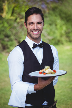 hotel staff: Handsome waiter holding a plate outside Stock Photo