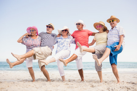 women friends: Happy senior friends dancing on the beach Stock Photo