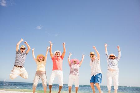 Happy senior friends jumping on the beach