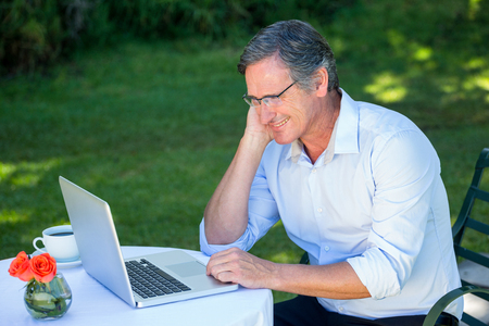daydreaming: Casual businessman using laptop daydreaming sitting on a terrace Stock Photo