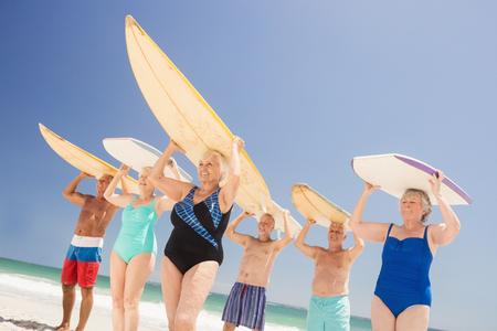 senior friends: Senior friends holding surfboard on the beach