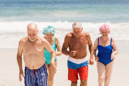 getting out: Senior friends getting out of water at the beach