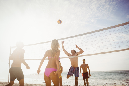 Glückliche Freunde, spielen Beach-Volleyball am Strand
