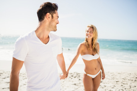 Smiling couple holding hands on the beach