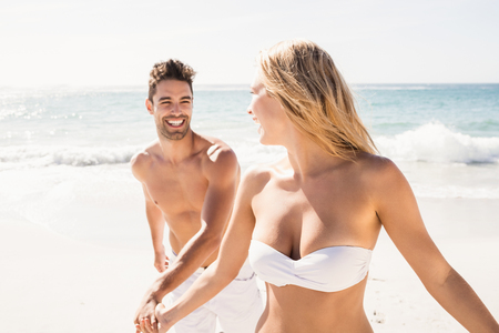 Mladý pár se drží za ruce na pláži