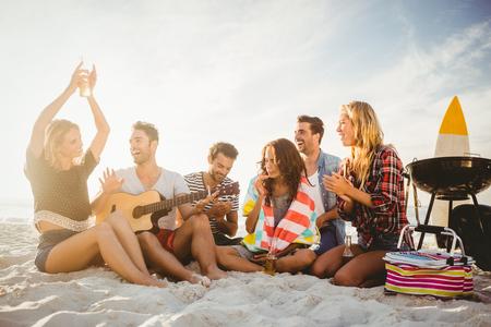 Amigos felices que se divierten cerca de la barbacoa en la playa