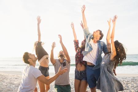 Amigos felices jugando voleibol de playa