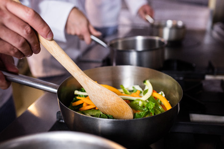 Close-up of chef preparing food in the kitchen of a restaurant